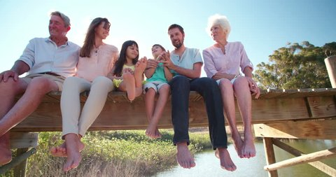 Three generation family outdoors on a summer vacation relaxing together on a jetty