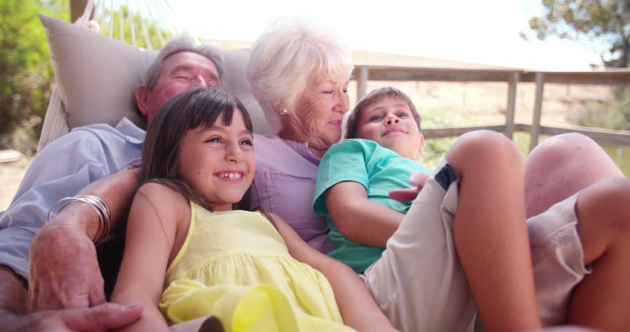 Loving grandparents spending time sitting with their grandchildren on their porch on a summer holiday in Slow Motion