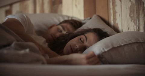 Young sleeping couple in bed
