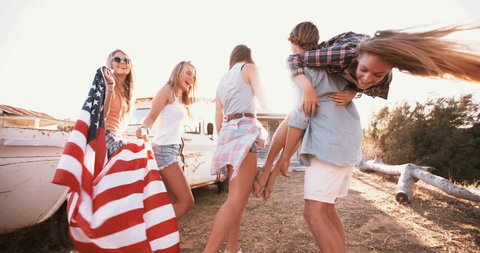 Full length shot of a group of American teens walking together with a flag over their shoulders into sun flare, Panning in Slow Motion