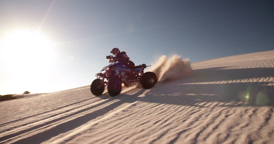 Competitive quad bike racer kicking up sand while driving up a sand dune on a summer evening with sun flare, Slow Motion, Panning