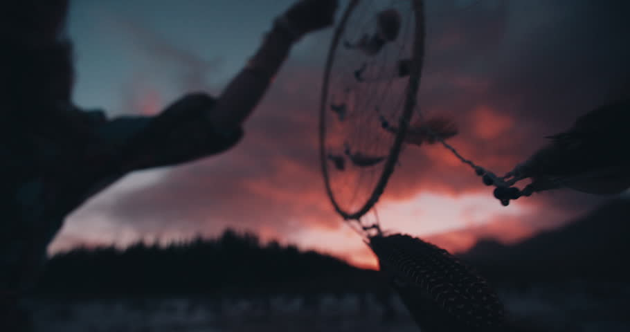 Boho style girl holding up a dream catcher and looking away wistfully on a summer evening