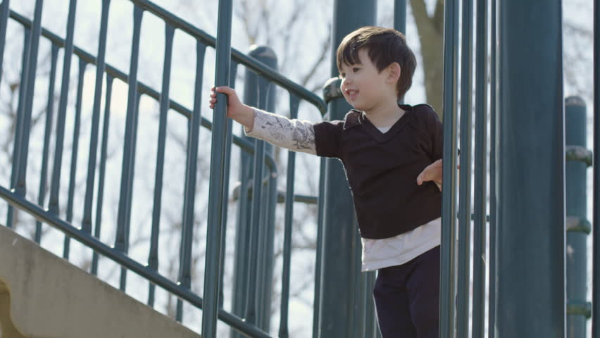 Mother gives her son a helping hand as he slides down a pole on a jungle gym in a park playground on a warm spring day.  Medium shot, recorded hand-held in slow motion at 4K at 60fps.