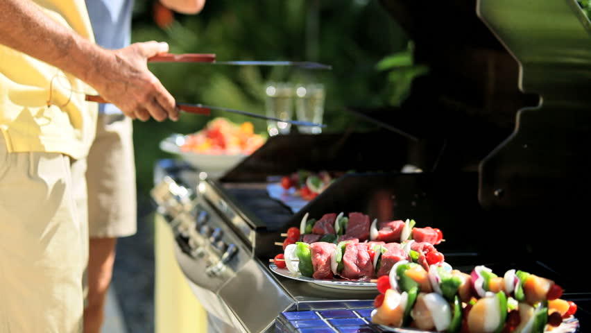 Senior couple cooking healthy grilled food on barbecue