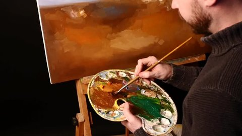 Talanted, bald, stylish, bearded painter in dark sweater with brush in his hand starts drawing an object painting by oil paints holding the palette in his hand on black background, back light, close