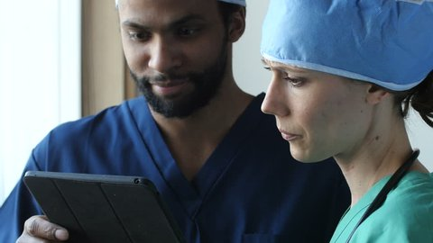 2 surgeons look at a tablet in a medical setting