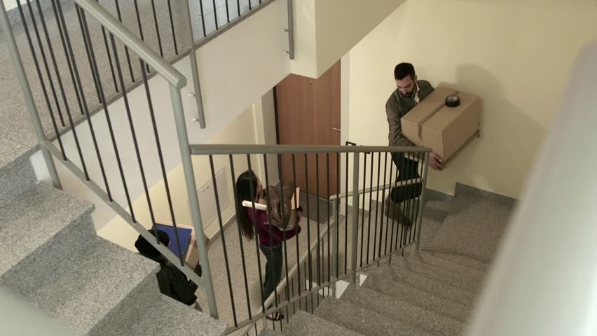 Group of three happy friends during move to new home, young people, students moving to new rental apartment with boxes, climbing stairs, going upstairs. 13 of 15