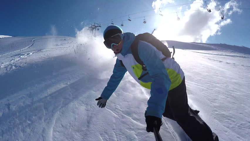 Snowboarder riding powder snow off piste in the mountains and doing powder turns #9891890