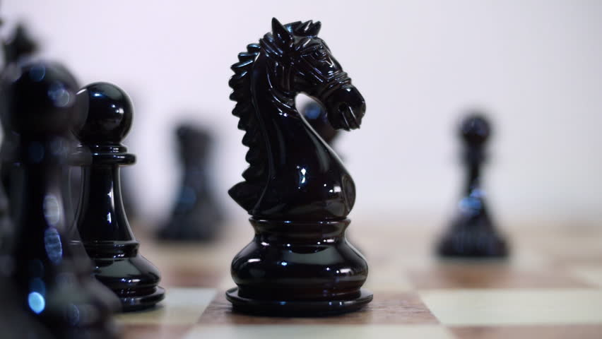 Chess Board and Pieces. Move black knight, horse. Closeup. Shallow depth of field. Dolly shot. Follow focus