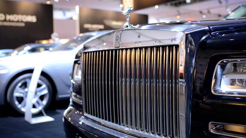 AMSTERDAM, THE NETHERLANDS - APRIL 16, 2015: Rolls Royce Ghost front grille with the Spirit of Ecstasy on top at the motor show. The camera is sliding from right to left.