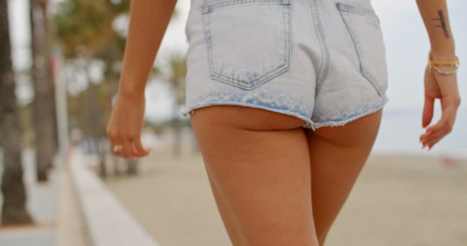 Rear View Close Up of Woman Wearing Denim Shorts Walking on Sidewalk  Womans Buttocks Peeking Out from Below Cut Off Shorts