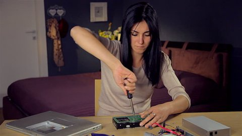 Cute woman trying to fix hard disk at home