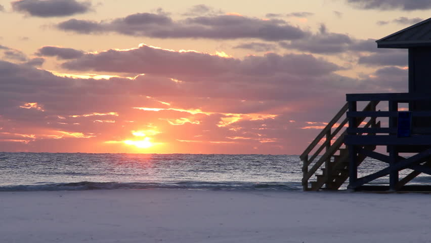 Glowing sunset make waves sparkle as they crest on a white beach.  Big sky with light rays streaming through clouds and a silhouette of a wooden structure.  Sand in foreground leaves a copy space.
