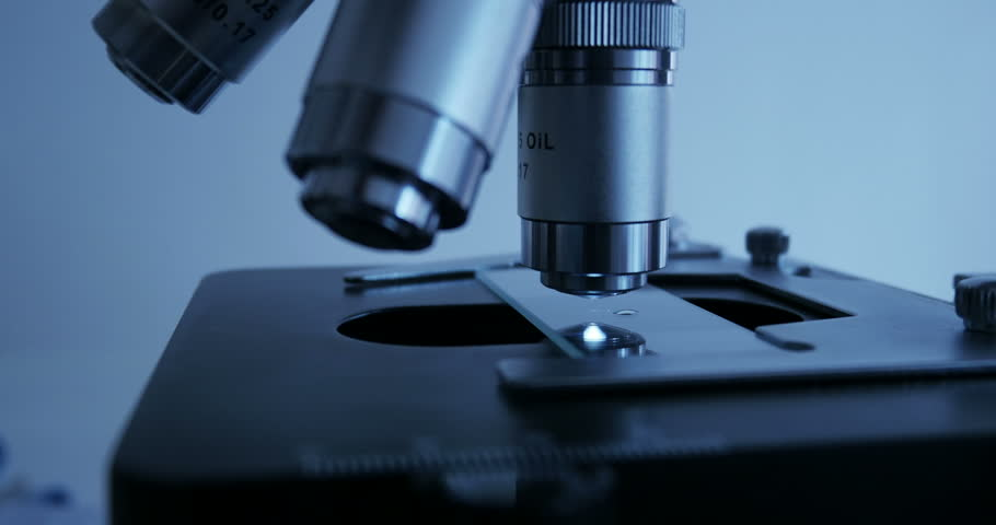 Scientist use a microscope in laboratory to focus it properly on a slide with a liquid substance. Shot on UHD 4K Production Digital Camera - easy to crop and edit | Shutterstock HD Video #9947690