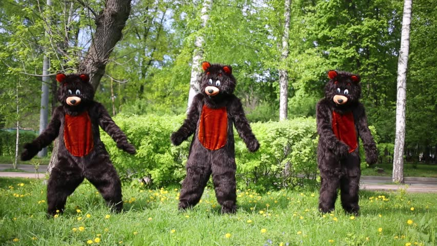 Three actors dressed in bear suits dance on grassy lawn at park.